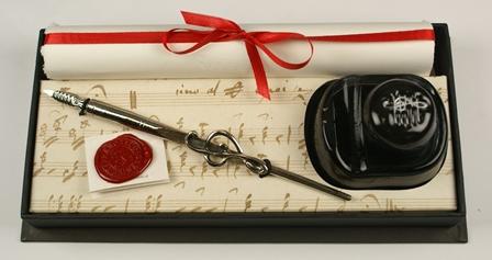 Violinkulcsos fémiron, tintával, piros selyemszalaggal átkötött merített papírral fekete díszdobozban
